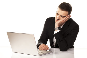 Young businessman has fallen asleep on his arm behind his laptop