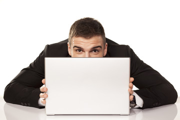 young and funny businessman hiding behind his laptop