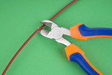 Metal nippers is cutting red cable on green  background poster