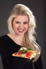 Junge blonde Frau bietet Pizza an und lächelt