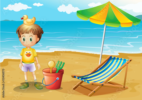A young boy and his toys at the beach