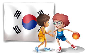 Two boys playing basketball in front of the Korean flag