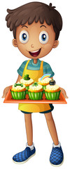 A young man holding a tray with cupcakes