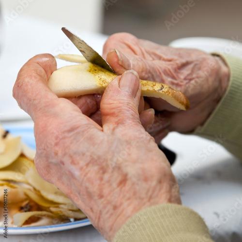 Personne âgée épluchant une poire