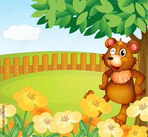 A bear standing near the flowers