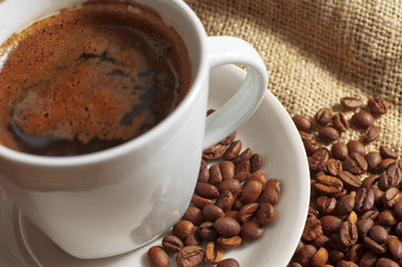 Closeup cup of coffee and coffee beans
