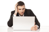 young businessman staring helplessly at his laptop poster