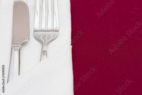 Shiny cutlery in folded white napkin on red tablecloth