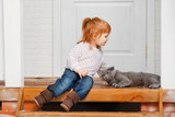 Little girl with a cat on a porch