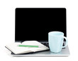 Tea cup and office supplies on laptop