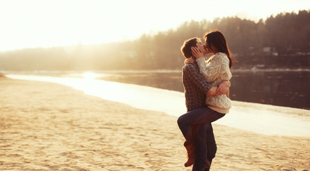 Young beautiful couple in love kissing on the beach on sunset
