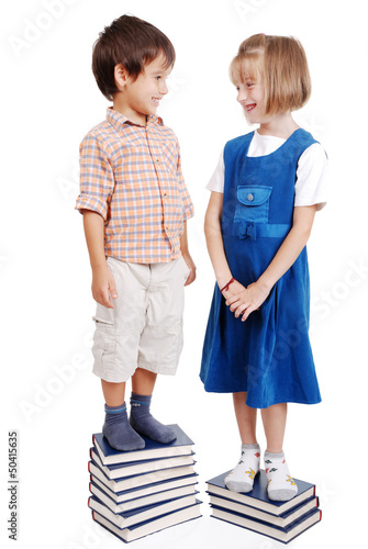 Two kids standing on pile of books