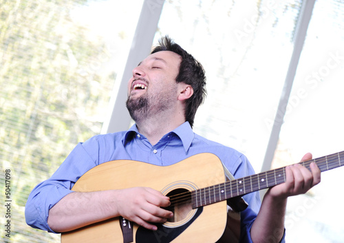 Male adult playing guitar