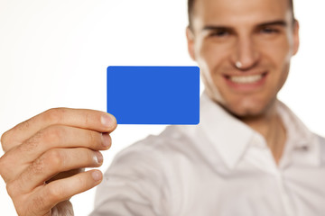 smiling attractive young man, holding a plastic card in his hand
