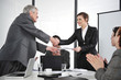 Business partners handshaking at meeting and receiving applause
