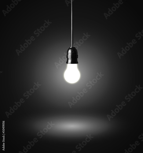 glowing hanging light bulb on a wire