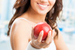 Woman with apple, at fitness center