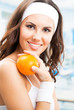 Woman with orange, at fitness center
