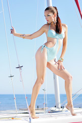 Graceful girl in blue swimsuit on sailboat