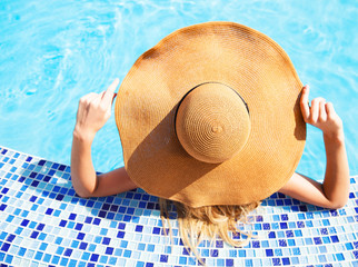 Woman in a hat enjoying a swimming pool
