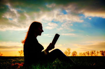 Teen girl reading book outdoors