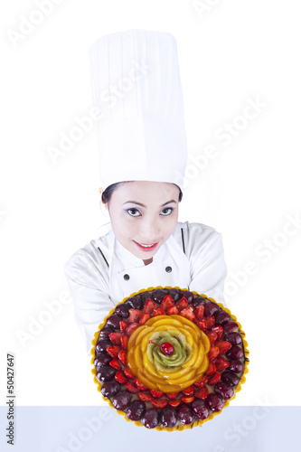 Chef serves fruit cake on white