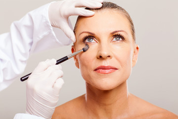 beautician putting makeup on mid age woman