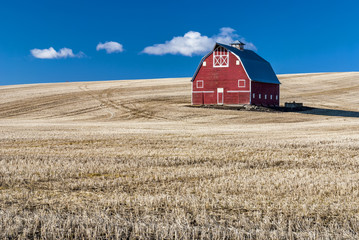 Red barn blue sky and wheat stuble field