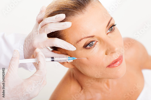 doctor giving mid age woman face lifting injection - 50428412