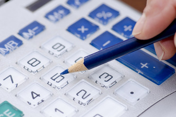 Calculator and pen adding accountant numbers