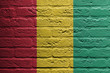 Brick wall with a painting of a flag, Guinea