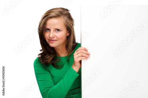 Young attractive girl behind empty board on white background