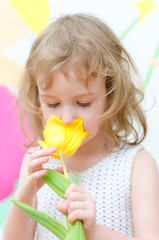 Cute little girl with yellow tulip