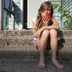 charming brunette girl biting green apple sitting on porch