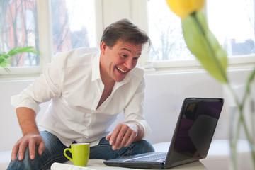 Lachender mann Zuhause am Laptop