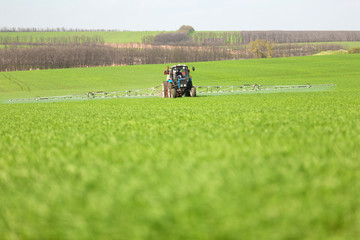 Tractor spraying a green field on a farm
