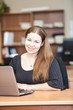 Happy smiling woman a brunette with laptop in office