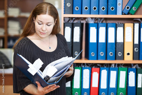 Business woman looking at documents in folder at office