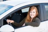 lächelnde junge frau in ihrem auto