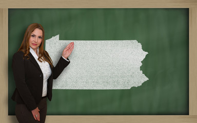 Teacher showing map of pennsylvania on blackboard