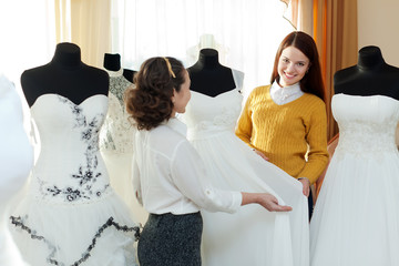 saleswoman helps girl chooses  bridal outfit