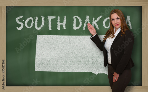 Teacher showing map of south dakota on blackboard
