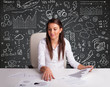 Businesswoman sitting at desk with business scheme and icons