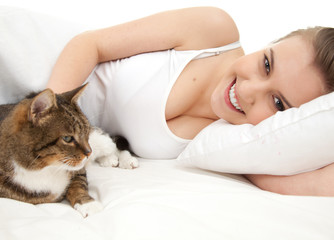 beautiful girl lyng in white bedding with cat