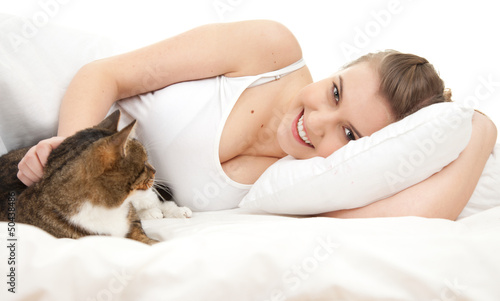 smiling teenage girl with cat relaxing in white bedding