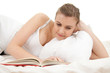 student woman reading book in white bedding