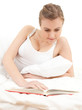 student girln reading book in white bedding