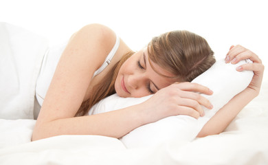 teenage girl sleeping in white bedding