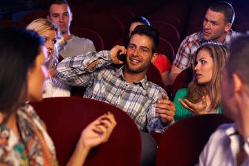 Confident young man using mobile in cinema
