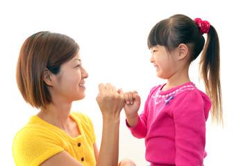 指きりをして微笑む親子